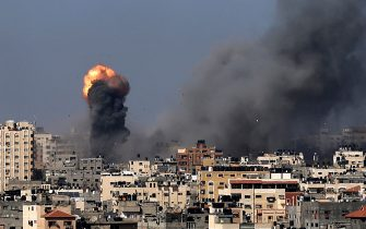"""Smoke billows following Israeli airstrikes on Gaza City on May 12, 2021, amid the most intense Israeli-Palestinian hostilities in seven years. - Israel's Defence Minister Benny Gantz vowed more attacks on Palestinian militant groups in Gaza to bring """"total, long-term quiet"""" before considering a ceasefire. (Photo by MAHMUD HAMS / AFP)"""