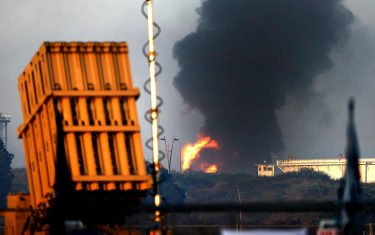 """An Iron Dome aerial defence system battery is seen in the foreground (L) as fire rages early on May 12, 2021 at Ashkelon's refinery, which was hit by Hamas rockets the previous day, in the southern Israeli city. - Intense fighting between Palestinian militants and the Israeli army continued overnight, after Israel's prime minister warned the Hamas movement that they will pay a """"heavy price"""" for firing rockets from Gaza into Israel. (Photo by JACK GUEZ / AFP)"""