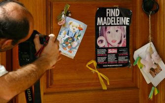 LAGOS, PORTUGAL - AUGUST 10:  A photographer takes a photograph of a poster and cards placed on the Church door in Praia da Luz for missing Madeleine McCann August 10, 2007 in Praia da Luz, Portugal. Police are continuing  their investigations in the Algarve village after blood was found in the McCann Apartment.  (Photo by Jeff J Mitchell/Getty Images)