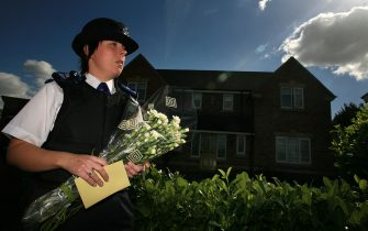 ROTHLEY, UNITED KINGDOM - SEPTEMBER 10:  A police officer delivers flowers to the home of Gerry and Kate McCann on September 10, 2007 in Rothley, England. The McCanns returned from Portugal yesterday after local police questioned them and named them as formal suspects in the disappearance of their daughter Madeleine, 4,  who vanished from their holiday apartment in Praia da Luz, Portugal several months ago. Portugal's public prosecutor is due to review police papers detailing the Madeleine McCann inquiry. (Photo by Christopher Furlong/Getty Images)