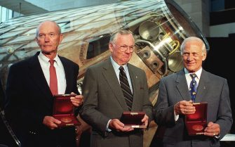 DCA01 - 19990720 - WASHINGTON, DC, UNITED STATES : The crew of Apollo 11 Michael Collins (L), Neil Armstrong (C) and Buzz Aldrin stand in front of the Apollo command module Columbia after US Vice President Al Gore awarded them the Samuel P. Langley medal 20 July, 1999 at the National Air and Space Museum in Washington, DC.  Armstrong was the first man to step on the moon 30 years ago 20 July 1969 followed by Aldrin while Collins remained in the orbiting command module.     EPA PHOTO AFP/JOYCE NALTCHAYAN