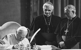 Pope John Paul II, seated at a table in the Old Consistorial Hall, signs the new Roman Catholic Code of Canon Law during a ceremony at the Vatican 1/25. The new Code of Canon Law is a more streamlined set of Church law that retains automatic excommunication for abortion and makes marriage annulments more complex. In center West German Cardinal Joseph Ratzinger, and at right Venezuelan Archbishop Rosalio Jose Castillo Lara, Chairman of the Vatican commission that has been revising the code for the last two decades.