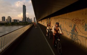 People go cycling and run on the Kaisermuhlenbrucke bridge crossing the Danube river, in late afternoon, in Vienna on August 3, 2015. AFP PHOTO/JOE KLAMARA.
