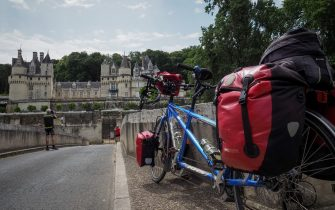 """A couple of German cyclists stop on the road named """"Loire a Velo"""", in front of  the Chateau d'Usse, in Rigny-Usse, on July 2, 2019. """"Loire a velo"""" is a 900-kilometres bicycle tour that links Cuffy to Saint-Brevin-les-Pins in the Loire-Atlantique Region. - France is the second largest destination in the world for cycling tourism with nearly 16,000 kilometres of itineraries. (Photo by GUILLAUME SOUVANT / AFP)        (Photo credit should read GUILLAUME SOUVANT/AFP via Getty Images)"""