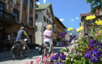 A couple cycles by traditional bavarian houses in the Partenkirchen quarter on June 4, 2015 in Garmisch-Partenkirchen, southern Germany.  Germany will host the G7 summit at Elmau Castle on June 7 and June 8, 2015. AFP PHOTO / PHILIPP GUELLAND        (Photo credit should read PHILIPP GUELLAND/AFP via Getty Images)