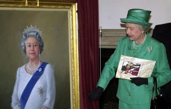 Queen Elizabeth II unveils a portrait of herself by artist Theodore Ramos at the Guildhall in Windsor, 03 June 2002, to mark her Golden Jubilee. A 1954 painting of the Queen hangs on the wall in the background.   (Photo credit should read MARTIN HAYHOW/AFP via Getty Images)