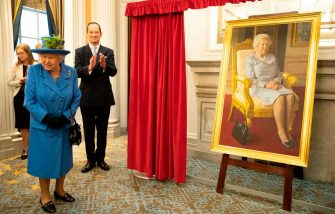 Britain's Queen Elizabeth II (L) unveils a portrait of herself painted by artist Benjamin Sullivan and commissioned to celebrate 100 years of the RAF Club during a visit to the club to mark its centenary year in London on October 17, 2018. - The Queen, visited the Royal Air Force Club to mark its centenary year. During the Queen officiall opened its new wing and unveiled a series of newly-commissioned artworks including a stained glass window and a portrait of Her Majesty. (Photo by Heathcliff O'Malley / POOL / AFP)        (Photo credit should read HEATHCLIFF O'MALLEY/AFP via Getty Images)