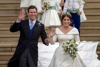 TOPSHOT - Britain's Princess Eugenie of York (R) and her husband Jack Brooksbank wave as they emerge from the West Door of St George's Chapel, Windsor Castle, in Windsor, on October 12, 2018 after their wedding ceremony. (Photo by Steve Parsons / POOL / AFP)        (Photo credit should read STEVE PARSONS/AFP via Getty Images)
