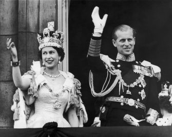 2nd June 1953:  Queen Elizabeth II and the Duke of Edinburgh wave at the crowds from the balcony at Buckingham Palace.  (Photo by Keystone/Getty Images)