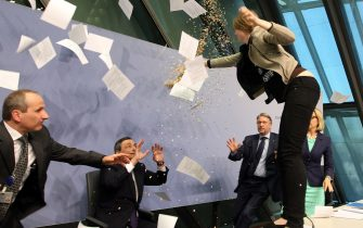 """A woman jumped on the table throws papers and confetti as she disrupts a press conference by Mario Draghi (C), President of the European Central Bank, (ECB) following a meeting of the Governing Council ain Frankfurt / Main, Germany, on April 15, 2015. The woman who charged at Draghi calling for an """"end to the ECB dictatorship"""" was quickly escorted out of the premises by security officers before the news conference resumed. AFP PHOTO / DANIEL ROLAND        (Photo credit should read DANIEL ROLAND/AFP via Getty Images)"""