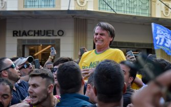 """TOPSHOT - Brazilian right-wing presidential candidate Jair Bolsonaro gestures after being stabbed in the stomach during a campaign rally in Juiz de Fora, Minas Gerais State, in southern Brazil, on September 6, 2018. - Frontrunner Bolsonaro was attacked with a knife while campaigning -- but escaped with just minor injuries, his son said. (Photo by Raysa LEITE / AFP) / RESTRICTED TO EDITORIAL USE - MANDATORY CREDIT """"AFP PHOTO /RAYSA LEITE"""" - NO MARKETING NO ADVERTISING CAMPAIGNS - DISTRIBUTED AS A SERVICE TO CLIENTS        (Photo credit should read RAYSA LEITE/AFP via Getty Images)"""