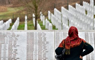 """A Bosnian Muslim woman, walks by the memorial wall containing the names of the victims at the Srebrenica memorial in Potocari, on March 20, 2019, on the day of the final sentence handed down in the case of Bosnian Serb wartime leader Radovan Karadzic before the Mechanism for International Criminal Tribunals (MTPI) in The Hague. - Former Bosnian Serb leader Radovan Karadzic will spend the rest of his life in jail for the """"sheer scale and systematic cruelty"""" of his crimes in the war that tore his country apart a quarter of a century ago, UN judges said on March 20, 2019. Grim-faced and silent, the 73-year-old stood in the dock as judges in The Hague said they had upheld his 2016 convictions for genocide in the Srebrenica massacre and war crimes throughout the 1990s. (Photo by ELVIS BARUKCIC / AFP)        (Photo credit should read ELVIS BARUKCIC/AFP via Getty Images)"""