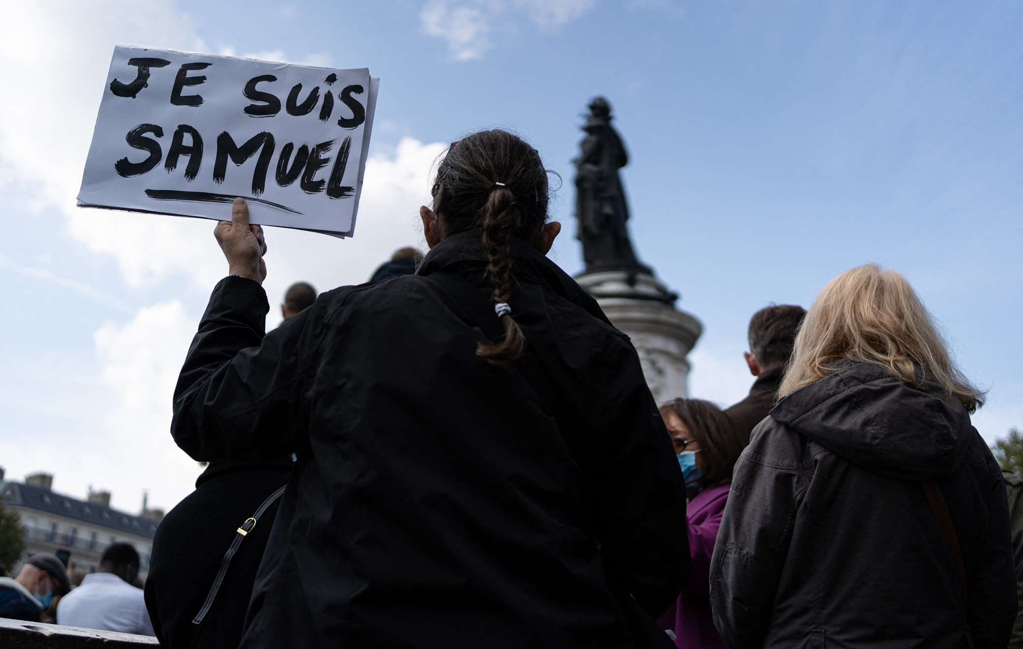 """A woman holds a sign saying """"I am Samuel"""". People are demonstrating in Republic Square at the call of Charlie Hebdo and SOS Racism to pay tribute to Professor Samuel Paty, assassinated Friday for showing his students caricatures of Mohammed. Paris, France, October 18, 2020. Photo by Florent Bardos/ABACAPRESS.COM"""