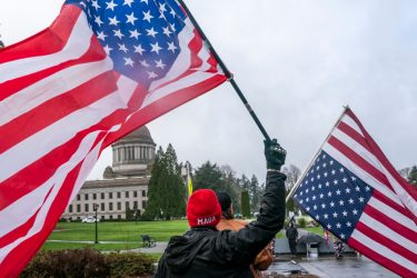 OLYMPIA, WA - FEBRUARY 06: A self-identified member of the Patriot movement flies an upside down American Flag on February 6, 2021 in Olympia, Washington. Right-wing protesters have been mostly quiet in the West following the inauguration of President Joe Biden. (Photo by Nathan Howard/Getty Images)