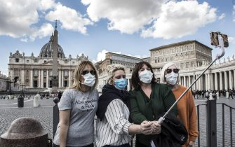 ROME, ITALY - MARCH 08: Tourists wearing protective masks take a selfie on March 08, 2020 in St. Peter's Square at the Vatican, Italy. Italian government has placed nearly a quarter of italian population in quarantine mostly in Northern Italy in the Region of Lombardy, and at least 15 italian provinces including the cities of Modena, Parma, Piacenza, Reggio Emilia, Rimini, Pesaro, Urbino, Venice, Padua Treviso, Asti, Vercelli, Novara, Verbano Cusio Ossola e Alessandria.(Photo by Alessandra Benedetti - Corbis/Getty Images)