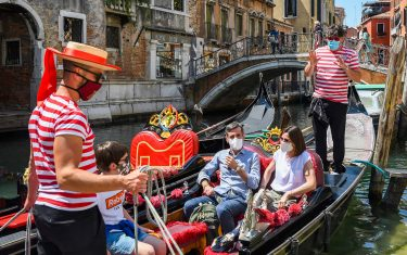 TOPSHOT - Gondoliers go with customers for a gondola ride on a canal in Venice on June 12, 2020 as the country eases its lockdown aimed at curbing the spread of the COVID-19 infection, caused by the novel coronavirus. (Photo by ANDREA PATTARO / AFP) (Photo by ANDREA PATTARO/AFP via Getty Images)
