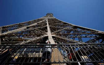 A visitor wearing a protective facemask admires the view from the Eiffel Tower during its partial reopening on June 25, 2020, in Paris, as France eases lockdown measures taken to curb the spread of the COVID-19 caused by the novel coronavirus. - Tourists and Parisians will again be able to admire the view of the French capital from the Eiffel Tower after a three-month closure due to the coronavirus -- but only if they take the stairs. (Photo by Thomas SAMSON / AFP) (Photo by THOMAS SAMSON/AFP via Getty Images)