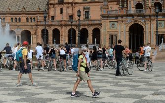 A tourist wearing a protective mask walks at Plaza de Espana in Seville on March 11, 2020 after Spain banned all air traffic from Italy, closed schools and blocked fans from football matches due to the coronavirus outbreak. - Coronavirus infections in Spain have passed the 2,000 mark with 47 deaths, the health ministry announced, making it Europe's second most severe outbreak after Italy. (Photo by CRISTINA QUICLER / AFP) (Photo by CRISTINA QUICLER/AFP via Getty Images)