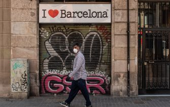 BARCELONA, SPAIN - MAY 06: A man wearing a protective face mask walk past a closed souvenir shop on May 06, 2020 in Barcelona, Spain. Despite of small businesses are allowed to open since last Monday, many shops and restaurants remain closed. Spain is opening businesses such as hairdressers, delivery food restaurants and book shops after weeks of lockdown. Spain has had more than 218,000 confirmed cases of COVID-19 and over 25,000 reported deaths, although the rate has declined due to lockdown measures. (Photo by David Ramos/Getty Images)