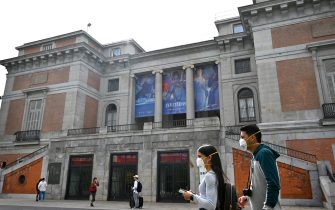 Tourists wearing protective face masks walk in front of El Prado museum in Madrid on March 12, 2020, after all of Madrid's state-run museums were closed to the public due to the coronavirus outbreak. - Spain struggles to handle a quadrupling of cases in three days, taking the number of infections above 2,000 and 48 dead, with Madrid the worst-hit area accounting for more than half of the cases. (Photo by GABRIEL BOUYS / AFP) (Photo by GABRIEL BOUYS/AFP via Getty Images)