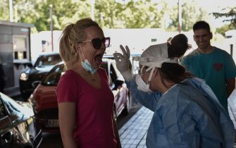 A public health worker collects a swab sample from a woman to test for the COVID-19 coronavirus at the Greek-Bulgarian border crossing in Promachonas on June 19, 2020. - Thousands have already crossed the border with Bulgaria, the first overland checkpoint opened by Greek authorities on June 15 after the coronavirus lockdown in March to reach tourist destinations in northern Greece. (Photo by Sakis MITROLIDIS / AFP) (Photo by SAKIS MITROLIDIS/AFP via Getty Images)