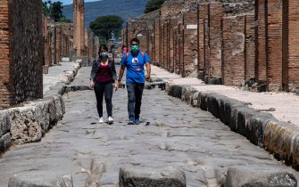 Visitors wearing a face mask walk across the archeological site of Pompeii on May 26, 2020, as the country eases its lockdown aimed at curbing the spread of the COVID-19 infection, caused by the novel coronavirus. - Italy's world-famous archeological site Pompeii reopened to the public on May 26,bBut with foreign tourists still prohibited from travel to Italy until June, the site that attracted just under 4 million visitors in 2019 is hoping that for now, Italian tourists can make up at least a fraction of the difference. (Photo by Tiziana FABI / AFP) (Photo by TIZIANA FABI/AFP via Getty Images)