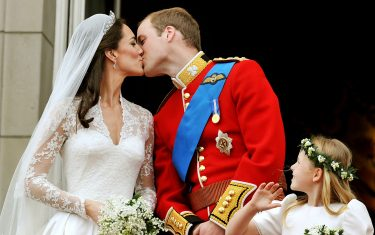 Prince William and his wife Kate Middleton, who has been given the title of The Duchess of Cambridge, kiss on the balcony of Buckingham Palace, London, following their wedding at Westminster Abbey.  PRESS ASSOCIATION Photo. Picture date: Friday April 29, 2011. See PA story WEDDING Lead. Photo credit should read: John Stillwell/PA Wire