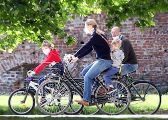 """Una famiglia  in bicicletta al parco Sempione di Milano  nel primo giorno della """"Fase2"""" determinata dall'emergenza del Coronavirus. Milano 4 Maggio 2020.ANSA / MATTEO BAZZI"""