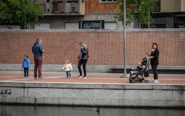 Genitori e figli bambini a passeggio sulla Darsena durante il lockdown per l emergenza epidemia coronavirus Covid-19, Milano, 26 aprile 2020.  Ansa/Matteo Corner