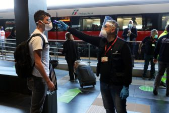 REGGIO CALABRIA, ITALY - JUNE 4: A passenger has his temperature checked as they prepare to board the first Freccia Rossa high speed long haul train connecting Reggio Calabria and Turin in the history of the Italian railway system as it prepares to leave the station on June 4, 2020 in Reggio Calabria, This is the longest high speed long haul connection in Europe, about 1300 km and the journey takes 11 hours. Italy has reopened its borders and ended travel restrictions between regions, hoping to encourage tourists back in time for the summer. The country was the first in Europe hit hard by the outbreak and has recorded more than 33,000 deaths. (Photo by Marco Di Lauro/Getty Images)