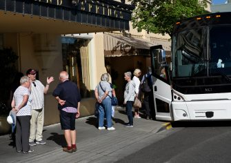 ASHLAND, OREGON - JUNE 19, 2019: A group of British tourists prepare to board their chartered tour bus in front of a hotel in Ashland, Oregon. The motor coach was manufactured by MCI (Motor Coach Industries). (Photo by Robert Alexander/Getty Images)