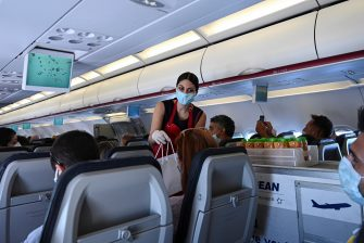 """A cabin crew member wearing a protective facemask serves passengers aboard of a flight to the island of Santorini on June 13, 2020 as the country prepares for the return of tourists to Greece from around 30 countries by air, sea and land. - From the emblematic island of Santorini, Greek Prime Minister said on June 13 that Greece is """"ready to welcome tourists"""" in complete safety after the coronavirus lockdown, whose impact on tourism will be """"significant"""". With its postcard landscape splashed with sunshine, the island of Santorini, one of the most touristic in Greece, awaits the return of tourists on June 15, divided between impatience to revive its effervescence and fear of seeing the coronavirus emerge from which it had so far been preserved. (Photo by ARIS MESSINIS / AFP) (Photo by ARIS MESSINIS/AFP via Getty Images)"""