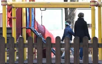 Una madre e il figlio, entrambi con il volto coperto da una mascherina sanitaria, in un parco giochi di quartiere che non è stato chiuso in prossimità di casa, Milano, 1 aprile 2020. La circolare diffusa ieri dal Vimilnale che permette a solo genitore può camminare con i figli minori in prossimità della propria abitazione è stata fortremente criticata. ANSA/DANIEL DAL ZENNARO