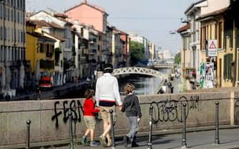 Una madre con i figli a passeggio in zona Navigli durante la fase 2 dell'emergenza Coronavirus a Milano, 6 maggio 2020.ANSA/Mourad Balti Touati