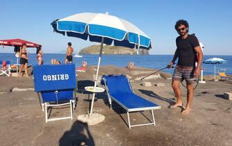 Un addetto alla manutenzione della spiaggia durante la sanificazione dei lettini alla scoglera del faro a Ventotene, 25 giugno 2020. ANSA/Lara Gallina