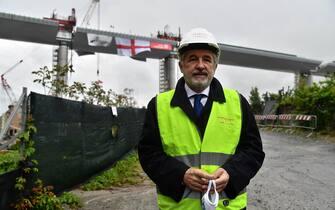 Il sindaco di Genova, Marco Bucci, con il volto coperto da una mascherina sanitaria, cammina nelle vicinanze dell'ultima parte di impalcato del ponte di Genova sul quale è stato appesa la croce di San Giorgio, la bandiera della città, Genova, 28 aprile 2020. ANSA/LUCA ZENNARO