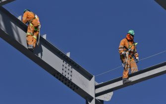 Steel workers walking on steel beams with safety attachment. (Photo by Giles Barnard/Construction Photography/Avalon/Getty Images)