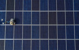 WUHAN, CHINA - MAY 15: A Chinese worker from Wuhan Guangsheng Photovoltaic Company works on a solar panel project on the roof of a 47 story building in a new development on May 15, 2017 in Wuhan, China. China consumes more electricity than any other nation, but it is also the world's biggest producer of solar energy. Capacity in China hit 77 gigawatts in 2016 which helped a 50% jump in solar power growth worldwide. China is now home to two-thirds of the world's solar production, though capacity and consumption remain low relative to its population.  Still, the country now buys half of the world's new solar panels à which convert sunlight into energy,  and are being installed on rooftops in cities and across sprawling fields in rural areas.  Greenpeace estimates that by 2030, renewable energy could replace fossil fuels as China's primary source of power, a significant change in a country considered the world's biggest polluter.  China's government has officially committed to development of renewable energies to ease the countryàs dependence on coal and other fossil fuels, though its strategic investments in the solar panel have created intense global competition. (Photo by Kevin Frayer/Getty Images)