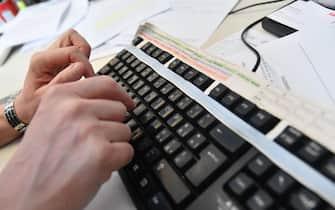 Un impiegato lavora al computer nel suo ufficio, 19 marzo 2018 a Genova. ANSA/LUCA ZENNARO
