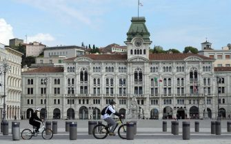 epa08387064 A handout photo made available by the Regione Friuli Press Office shows shows a father with son wearing face masks enjoing a bicycle ride in front of the Palazzo del Municipio (city hall) in Trieste, northeast Italy, 27 April 2020, during the coronavirus disease (COVID-19) pandemic.  EPA/GIOVANNI MONTENERO/REGIONE CRONACHE AGENCY/REGIONE FVG HANDOUT  HANDOUT EDITORIAL USE ONLY/NO SALES