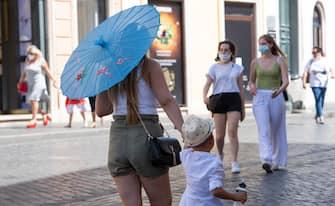 Turisti con le mascherine camminano a Piazza di Spagna a Roma, 30 luglio 2020.MAURIZIO BRAMBATTI/ANSA