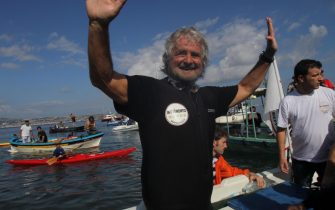 "Beppe Grillo greets before cross over Messina Strait, from Reggio Calabria to Messina coast 10 October, 2012. Italian showman and ""Movement 5 Stars"" leader, swimmed throw the Sicilian Strait to start the official M5 Party electioneering.  Il comico Beppe Grillo, fondatore del movimento 5 stelle, prima di attraverserà a nuoto lo Stretto di Messina FOTO ANSA/FRANCO CUFARI"