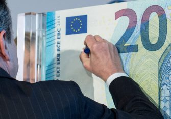 ECB President Mario Draghi presents the new 20 euro note in the ECB in Frankfurt am Main, Germany, 24 February 2015. Draghi signs an over-sized representation of the note. The design of the note will be changed and will include additional security features. Photo: BORIS ROESSLER/dpa