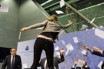 Eine Aktivistin stË rt die Pressekonferenz der Europâ °ischen Zentralbank (EZB). Sie springt auf den Tisch und bewirft EZB-Prâ °sident Mario Draghi mit Konfetti. Auf ihrem T-Shirt ist zu lesen: ECB dick-tatorship . Zuvor hatte Draghi verk¸ndet, den Leitzins auf dem Rekordtief von 0,05 Prozent zu belassen. EZB-Prâ °sident Mario Draghi wird umgehend von Personensch¸tzern aus dem Raum gef¸hrt. Die Frau wird abgef¸hrt. Nach einer kurzen Unterbrechung setzt Draghi seine Ausf¸hrungen zu den Entscheidungen des EZB-Rats fort. Berlin, 15.04.2015 Foto:xM.xGolejewskix/xFuturexImage  a Activist disturbs the Press conference the European Central Bank ECB Them jumps on the Table and bewirft ECB President Mario Draghi with Confetti on her T Shirt is to read ECB Thick  before had Draghi announced the Key on the Record low from 0 05 Percent to leave ECB President Mario Draghi will immediately from Personensch¸tzern out the Room led the Woman will removed after a short Interruption sets Draghi his Remarks to the Decisions the ECB Board Progress Berlin 15 04 2015 Photo XM