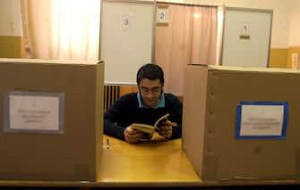 MI-3- 21/5/00- MILANO- POL- REFERENDUM; VOTANTI ALLE 12, TRA IL 7,1, IL 7,2%. Giornata di lavoro riposante per quetpo scrutinatore  di un seggio del centro di Milano intento a leggere dietro al tavolo di voto. Alle 12 per i sette referendum si è andato alle urne tra il 7,1, e il 7,2% degli aventi diritto . DAL ZENNARO/ANSA