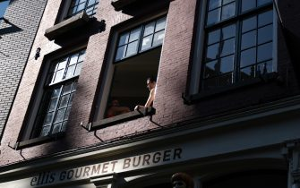AMSTERDAM, NETHERLANDS - MAY 9: People sit inside their house as they open a window above a closed burger shop on May 9, 2020 in Amsterdam, Netherlands. (Photo by Yuriko Nakao/Getty Images)