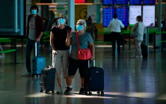 Passengers wearing face masks check their flight information on screens at the Josep Tarradellas Barcelona-El Prat airport in El Prat de Llobregat on July 6, 2020. - Spaniards endured one of the world's toughest lockdowns for three months from March as the country suffered one of Europe's worst coronavirus death tolls -- at least 28,385 -- and more than 250,000 cases. (Photo by Josep LAGO / AFP) (Photo by JOSEP LAGO/AFP via Getty Images)