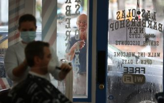 FORT LAUDERDALE, FLORIDA - MAY 18: James Bradford looks in the window at the Las Olas Barber shop as he hopes to get a haircut after it re-opened on May 18, 2020 in Fort Lauderdale, Florida. The barbershop re-opened, approximately two months after shutting it's doors due to the coronavirus pandemic, as Broward County starts the first phase of the states coronavirus pandemic re-opening plan, which includes openings with certain restrictions of businesses like barbershops, restaurants and retail stores. (Photo by Joe Raedle/Getty Images)