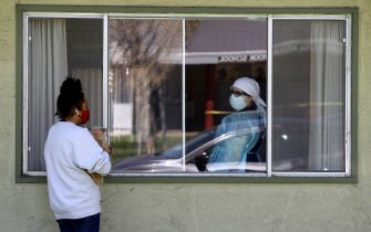 HAYWARD, CALIFORNIA - APRIL 14: Adrina Rodriguez (L) talks with a nurse through a window as she visits her father who is a patient at the Gateway Care and Rehabilitation Center that has tested negative for COVID-19 on April 14, 2020 in Hayward, California. The Gateway Care and Rehabilitation Center remains open after a tenth patient died from COVID-19 complications. (Photo by Justin Sullivan/Getty Images)