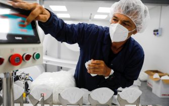 """A worker at the Sion Medical factory, the country's first production line of N95 masks, produces a mask at the factory in the southern Israeli city of Sderot on, June 15 2020. - Israel said it had opened a factory to make millions of high-spec masks as it prepares for a possible """"second wave"""" of coronavirus cases. """"We are preparing for a second wave of the virus,"""" said Defence Minister Benny Gantz, announcing the country's first production line of N95 masks. Gantz said the local production """"removes our dependence on foreign factors and contributes to the Israeli economy during a difficult period."""" (Photo by MENAHEM KAHANA / AFP) (Photo by MENAHEM KAHANA/AFP via Getty Images)"""
